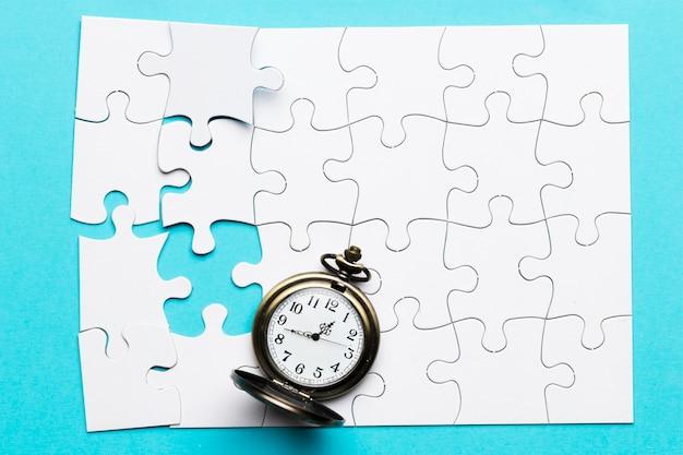 Retro stoppuhr auf unvollständigem weißem puzzlespiel über blauem hintergrund Kostenlose Fotos