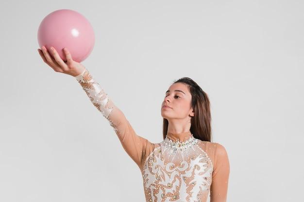 Rhythmischer turner, der mit der kugel aufwirft Kostenlose Fotos