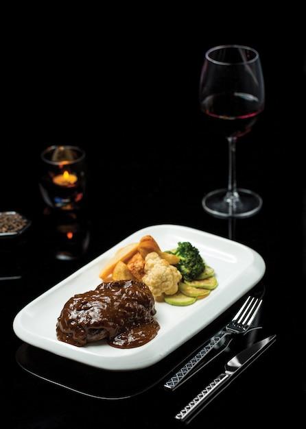 Ribeye-steak in teriyaki-sauce mit einem glas burgunder Kostenlose Fotos
