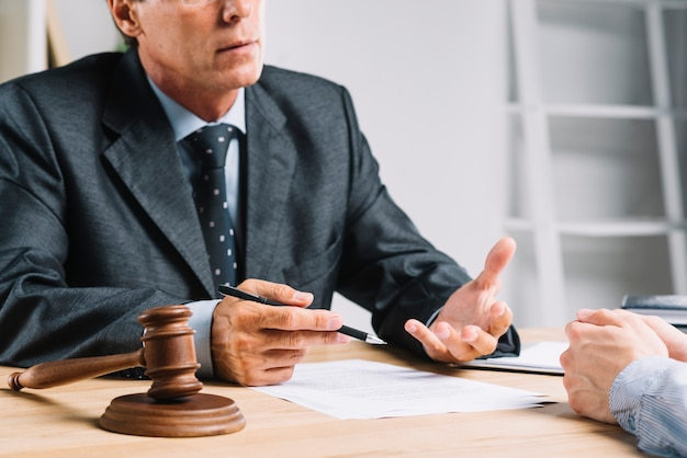 Richter, der mit seinem Kunden im Gerichtssaal diskutiert Kostenlose Fotos