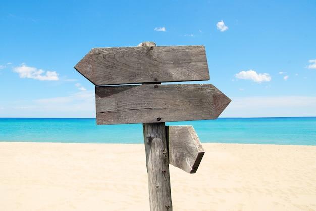 Richtungsverkehrsschild mit hölzernen pfeilen auf strand- und seehintergrund Premium Fotos