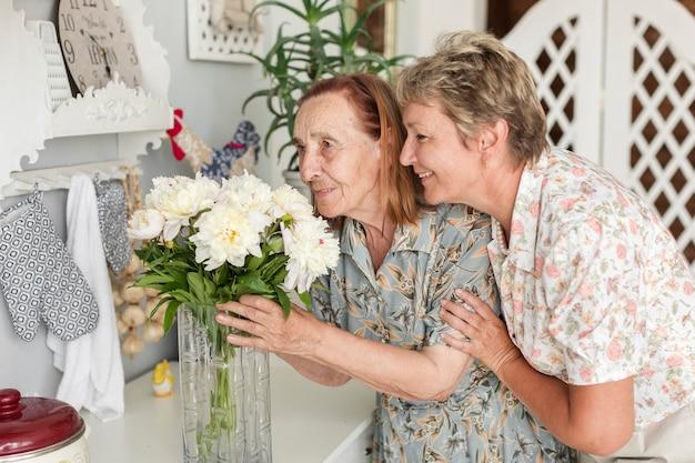 Riechende blumen der älteren mutter und der reifen tochter des vase zu hause Kostenlose Fotos