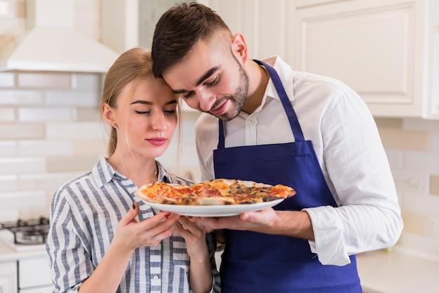 Riechende pizza der paare auf platte Kostenlose Fotos