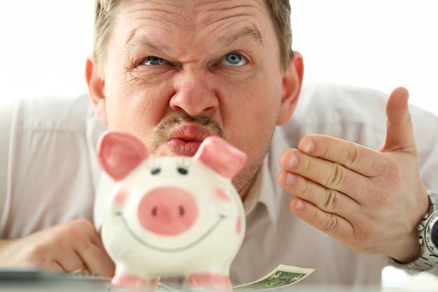 Riechender geruch des lustigen geschäftsmannes des geldes vom sparschwein Premium Fotos