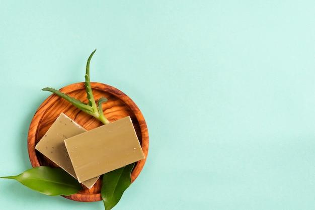 Riegel der grünen natürlichen olivenölseifen mit grünen blättern und aloe vera in einer platte auf blau Premium Fotos