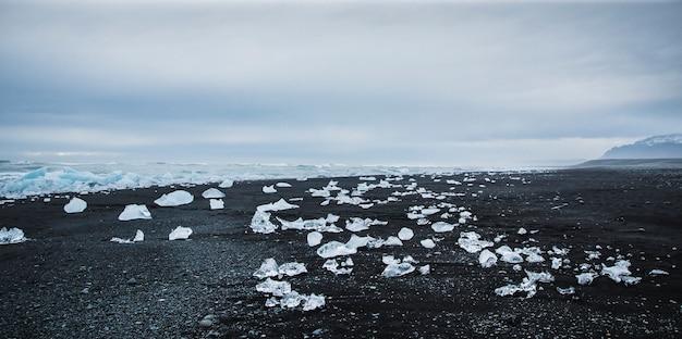 Riesige eisblöcke von eisbergen an der küste eines isländischen strandes abgelöst. Premium Fotos