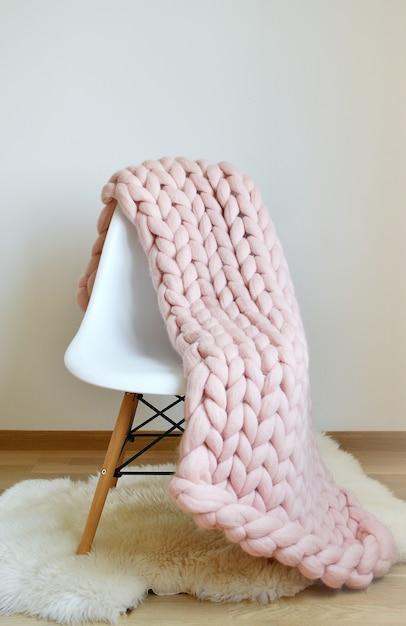 Riesige rosa plaid-decke woolen gestrickt auf weißer hölzerner schemel-stuhl-ausgangsskandinavier-art Premium Fotos