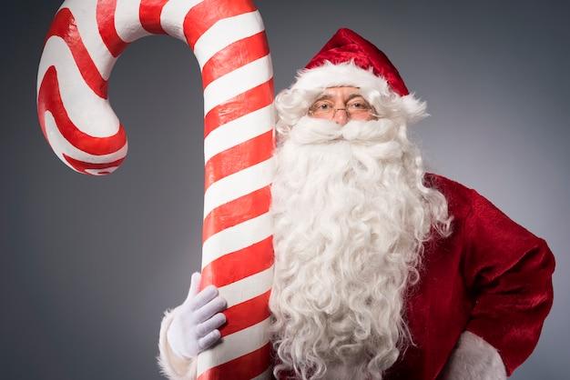 Riesige zuckerstange vom weihnachtsmann gehalten Kostenlose Fotos