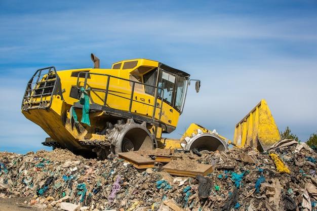 Riesiger bulldozer, der an der riesigen deponie oder müllkippe arbeitet, verschmutzungskonzept Premium Fotos