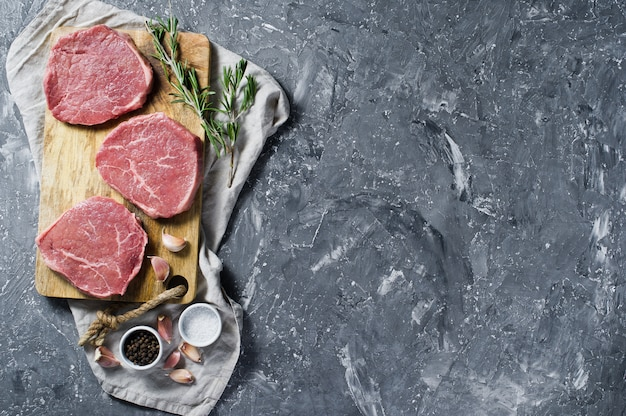Rinderfilet auf einem hölzernen schneidebrett, knoblauch und einem rosmarinzweig. Premium Fotos
