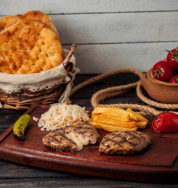 Rinderpastetchen mit käse gefüllt, serviert mit pommes frites, reis, tomaten und pfeffer Kostenlose Fotos
