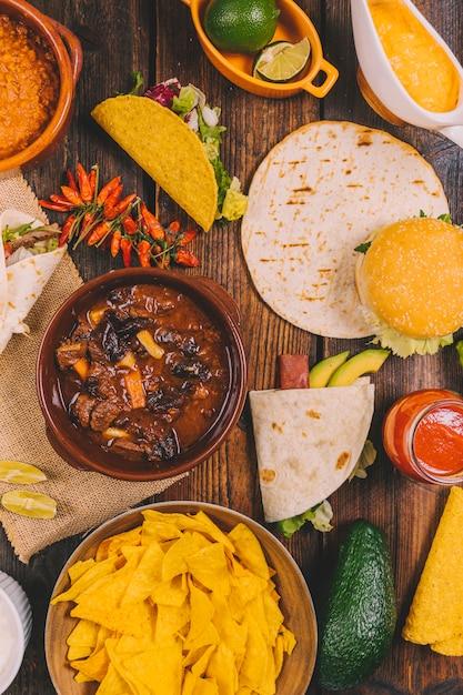 Rinderragout; tortilla; leckere mexikanische nachos; rote paprikaschoten; burger und avocado auf braunem tisch Kostenlose Fotos
