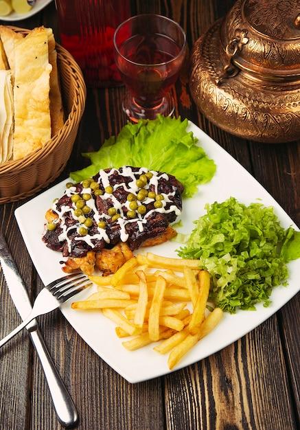 Rindersteak mit pommes frites, grünem salat, grünen bohnen und hühnernuggets. Kostenlose Fotos