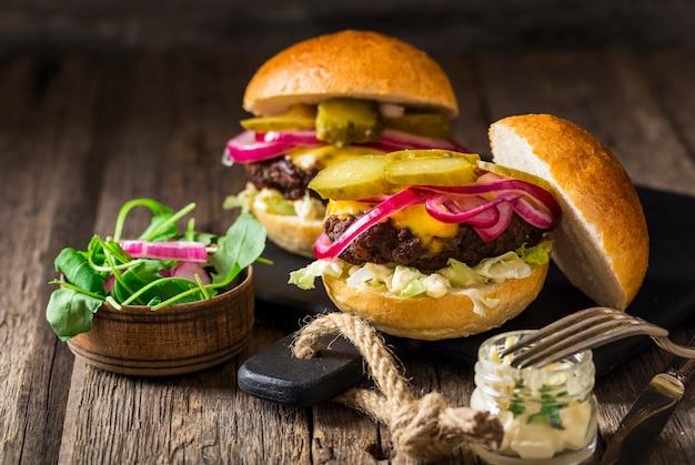 Rindfleisch-burger von vorne mit gurken und roten zwiebeln auf schneidebrett Kostenlose Fotos