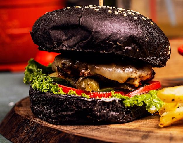 Rindfleisch-käseburger der schwarzen schokoladenwanne mit gemüseschnellimbiß. Kostenlose Fotos