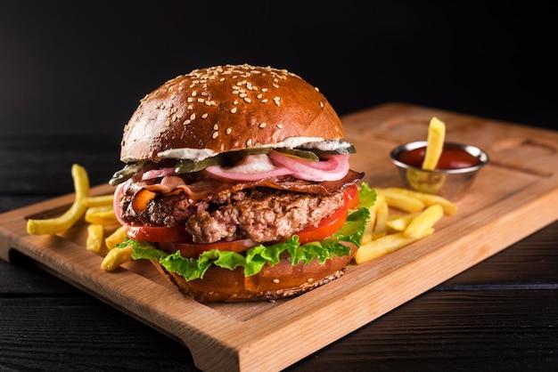 Rindfleischburger auf einem hölzernen brett mit pommes-frites Kostenlose Fotos