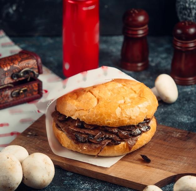 Rindfleischburger mit dem pilz, der in der papiertüte eingewickelt wurde, diente auf schneidebrett Kostenlose Fotos