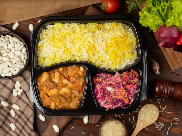 Rindfleischeintopf mit kartoffeln und kastanien in tomatensauce mit reisgarnitur und kohlkarottensalat zum mitnehmen Kostenlose Fotos