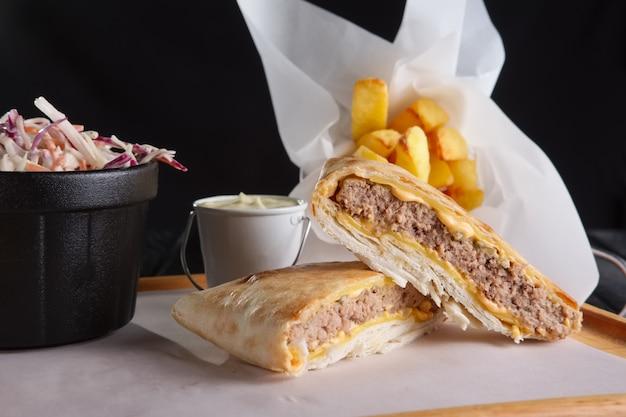 Rindfleischkotelett mit dem käse gerollt in pita mit gebratener kartoffel und rotkohl Premium Fotos