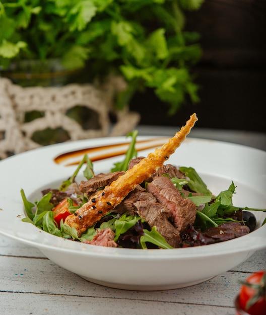 Rindfleischsalat mit rucola, tomaten und breadstick mit sesam Kostenlose Fotos