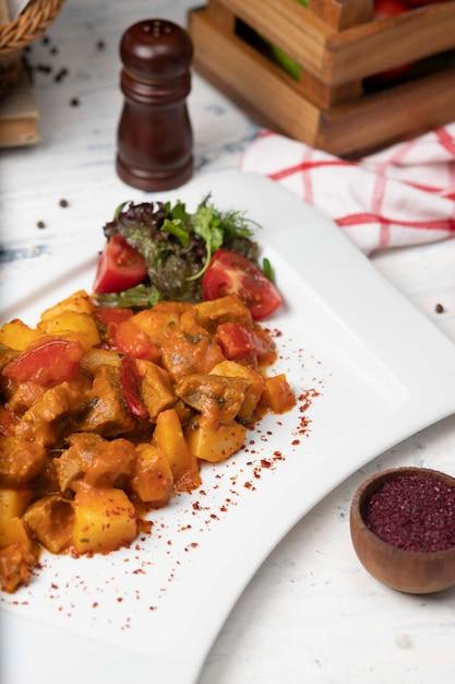 Rindfleischscheiben eintopf in tomatensauce mit zwiebeln und paprika. serviert in weißen teller mit basilikum, schwarzer pfeffer Kostenlose Fotos