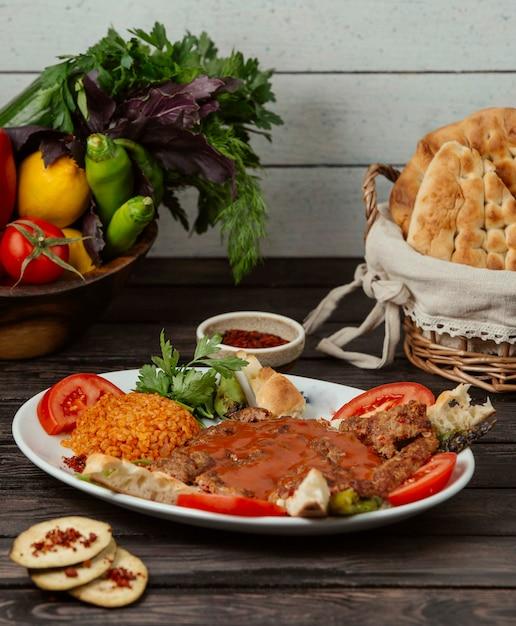 Rindfleischspiesse garniert mit tomatenscheibe, serviert mit bulgur, brot und gemüse Kostenlose Fotos
