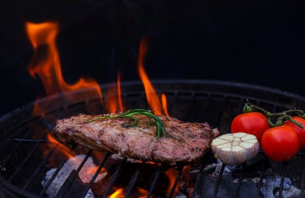Rindfleischsteak auf dem grillrost, flammen auf hintergrund Premium Fotos