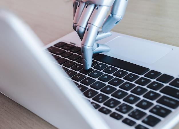 Roboterhände und -finger zeigen auf laptopknopfberater Premium Fotos