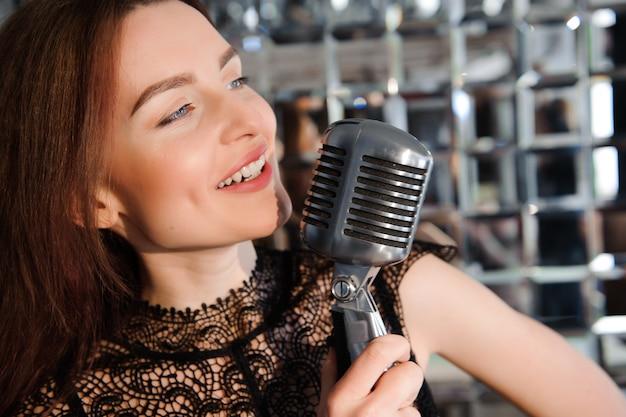 Rockstar, sexy mädchen, das im retro- mikrofon singt Premium Fotos