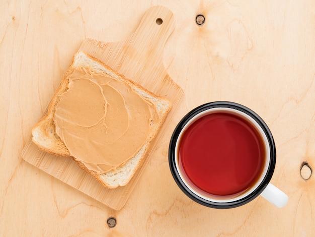 Rösten sie mit der erdnussbutter und auf sandwich verbreiten, becher tee auf einem beige hölzernen hintergrund Premium Fotos
