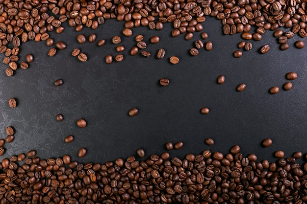 Röstkaffeebohnen des aromas auf rustikaler tischplatte, brauner fahnenhintergrund. Premium Fotos