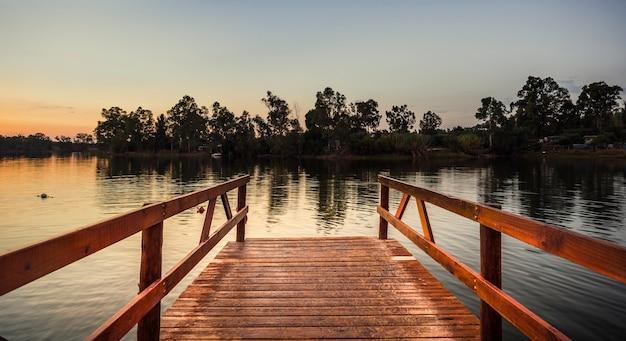 Rötlicher hölzerner pier über dem see mit ruhigem wasser bei sonnenuntergang Premium Fotos
