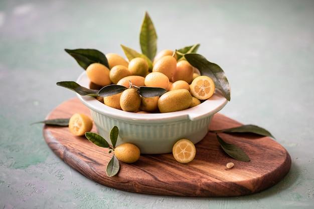 Rohe bio-orangen-kumquats in einer schüssel Kostenlose Fotos