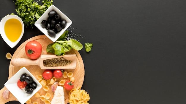 Rohe conchiglie teigwaren mit bestandteil über schwarzem hintergrund Kostenlose Fotos