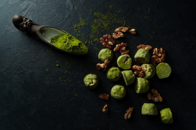 Rohe energiebälle mit matcha teepulver an auf dunklem hintergrund Premium Fotos