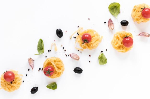 Rohe fettuccineteigwaren; kirschtomate; schwarze olive; knoblauchzehen- und basilikumblätter lokalisiert über weißem hintergrund Kostenlose Fotos