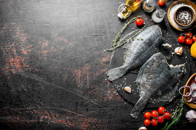 Rohe fischflunder mit gewürzen, tomaten, gehackten zwiebeln und knoblauch auf rustikalem tisch Premium Fotos
