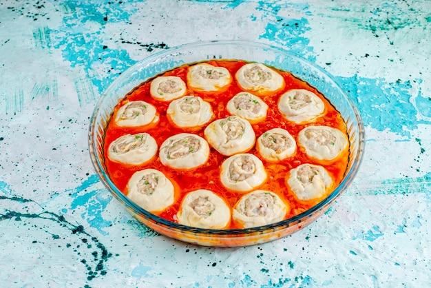 Rohe fleischige teigteigscheiben mit hackfleisch innen mit tomatensauce innen glaspfanne auf blau f Kostenlose Fotos