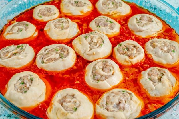 Rohe fleischige teigteigscheiben mit hackfleisch innen mit tomatensauce innen glaspfanne auf blau Kostenlose Fotos