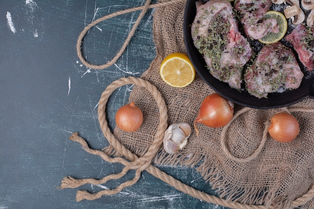 Rohe fleischstücke in schwarzer pfanne mit zwiebeln, knoblauch, zitrone und pilzen. Kostenlose Fotos