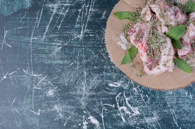 Rohe fleischstücke mit frischen und getrockneten kräutern auf blau. Kostenlose Fotos