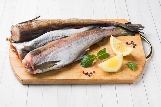 Rohe frische pollockfische auf einem hölzernen brett mit zitrone Premium Fotos