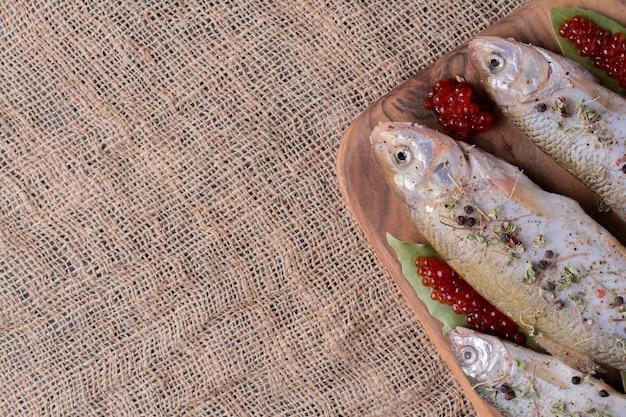 Rohe ganze fische mit rotem kaviar auf holzbrett. Kostenlose Fotos