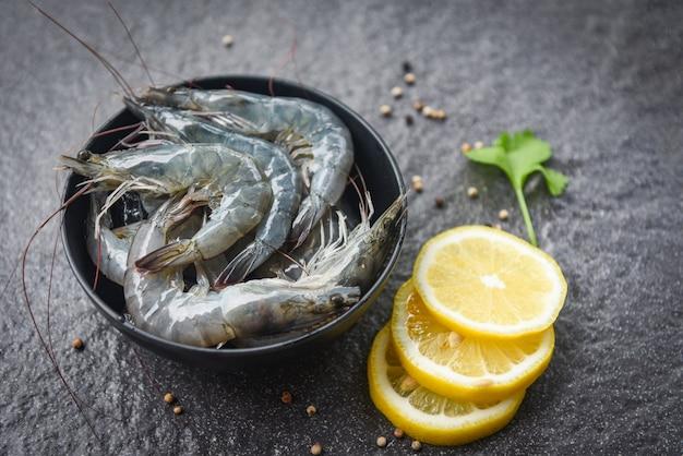 Rohe garnelen auf schüssel - frische garnelen zum kochen mit gewürzen zitrone und sellerie Premium Fotos