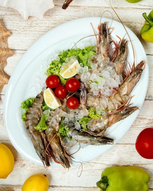 Rohe garnelen mit eis, garniert mit kirschtomaten, zitrone und salat Kostenlose Fotos
