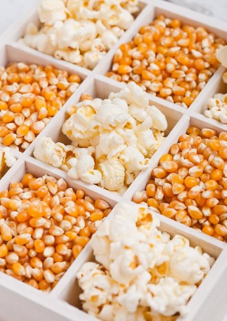 Rohe goldene zuckermais-samen und popcorn in der weißen holzkiste auf hellem hintergrund makro Premium Fotos