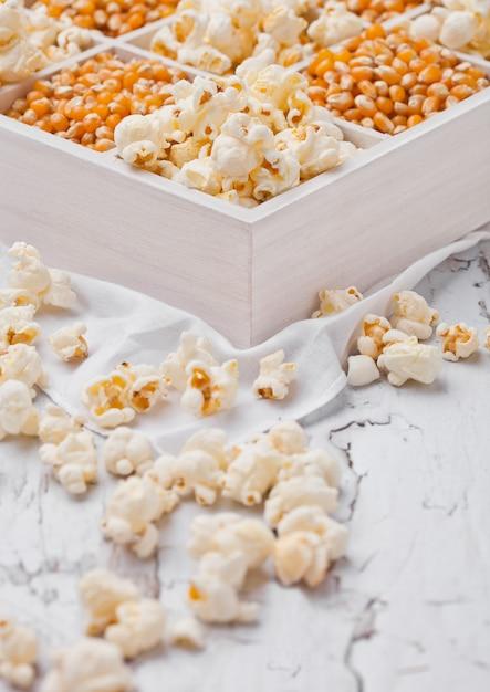 Rohe goldene zuckermais-samen und popcorn in der weißen holzkiste auf hellem hintergrund Premium Fotos