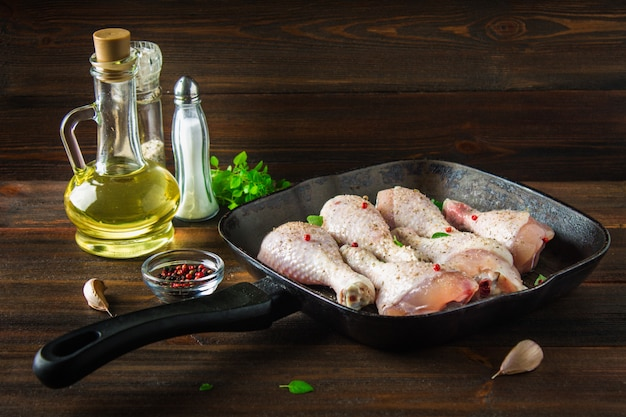 Rohe hühnerbeine in einer bratpfanne auf einem holztisch. fleischzutaten zum kochen. Premium Fotos