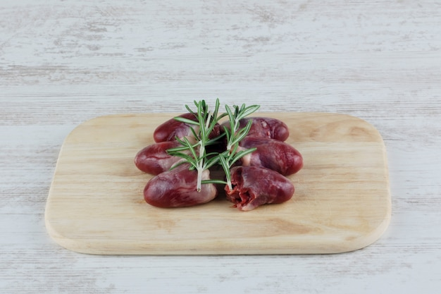Rohe hühnerherzen mit rosmarin auf hölzernem schneidebrett Premium Fotos