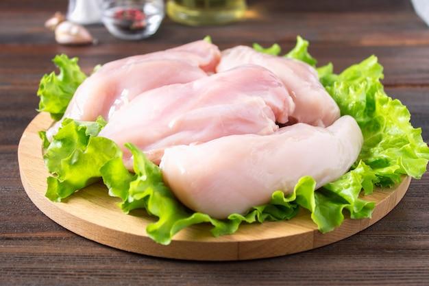 Rohe hühnerleiste und grüner salat auf einem runden schneidebrett auf einem holztischhintergrund. Premium Fotos
